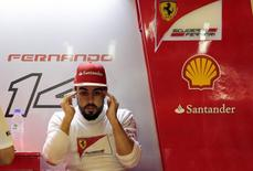 Ferrari Formula One driver Fernando Alonso of Spain sits in the Ferrari garage after his car broke down during the second practice session of the Abu Dhabi F1 Grand Prix at the Yas Marina circuit in Abu Dhabi November 21, 2014. REUTERS/Caren Firouz/Files
