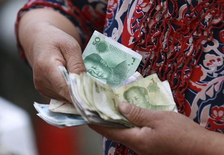 A vegetable vendor holds a stack of Chinese yuan banknotes at a morning market in Shenyang, Liaoning province June 10, 2014. REUTERS/Stringer