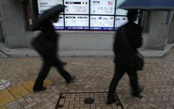 Pedestrians with umbrellas walk past an electronic board showing Japan's Nikkei average (top middle L) and the exchange rates between the Japanese yen and the U.S. dollar (top middle R), outside a brokerage in Tokyo November 11, 2014. REUTERS/Yuya Shino