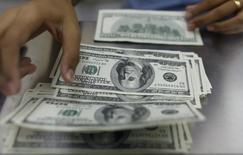 Сотрудник обменного пункта считает доллары. Фотография сделана в Янгоне 23 мая 2013 года. Банк России видит дефицит рублевой ликвидности, но считает эту ситуацию нормальной и управляемой, положение дел с валютной ликвидностью постепенно выровняется, но этот процесс будет длительным, а репо в иностранной валюте может в настоящее время полностью удовлетворить потребность участников рынка. REUTERS/Soe Zeya Tun