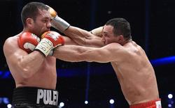 Ukrainian WBA, WBO, IBO and IBF heavyweight boxing world champion Vladimir Klitschko (R) lands a punch during his title fight against challenger Bulgarian heavyweight boxer Kubrat Pulev in Hamburg, November 15, 2014. REUTERS/Fabian Bimmer