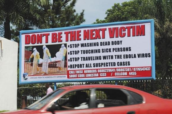 Um carro dirige passado uma propaganda de saúde pública contra o vírus Ebola em Monrovia 8 de outubro de 2014. REUTERS / James Giahyue