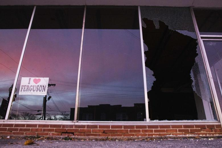 The sunrise is reflected in a shattered storefront following a second night of protests in Ferguson, Missouri November 26, 2014. REUTERS/Lucas Jackson