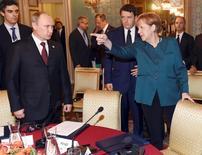 """Канцлер Германии Ангела Меркель (справа), президент России Владимир Путин (слева) и премьер-министр Италии Маттео Ренци на встрече в Милане 17 октября 2014 года. Канцлер Германии Ангела Меркель обвинила Россию в нарушении международного права на Украине и сказала, что урегулирование конфликта потребует терпения. Путин заочно ответил, что никому не угрожает, но заявил на встрече с генералами о намерении """"защитить безопасность наших союзников"""". REUTERS/Daniel Dal Zennaro/Pool"""