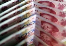 Купюры валюты юань в Пекине 22 марта 2011 года. Планы российских банков и компаний, попавших под санкции Запада, занять на азиатских рынках капитала, могут остаться планами. Юридическое оформление сделок недоступно, расчеты по ним заморожены, а местные банки отказываются помочь с размещением из-за риска быть наказанными громадными штрафами, говорят источники Рейтер. REUTERS/Jason Lee