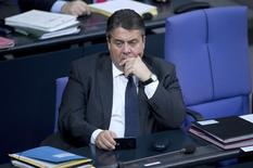 Germany's Economy Minister Sigmar Gabriel holds a MOBILE phone during a debate at the lower house of parliament Bundestag in Berlin, November 26, 2014.  REUTERS/Stefanie Loos
