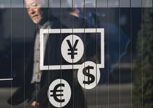 Символы доллара США, евро и иены на здании обменного пункта в Токио 27 ноября 2014 года. Доллар поднялся до семилетнего пика к иене, а швейцарский франк подешевел к евро, так как швейцарцы не поддержали идею увеличить золотые запасы центробанка. REUTERS/Issei Kato