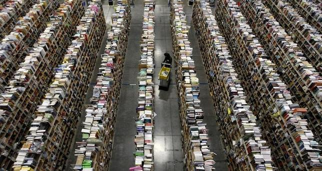 A worker gathers items for delivery from the warehouse floor at Amazon's distribution center in Phoenix, Arizona November 22, 2013.  REUTERS/Ralph D. Freso