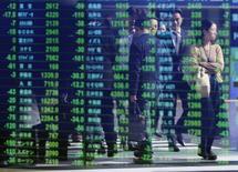 Transeúntes se ven reflejados en una pantalla electrónica que muestra índices económicos en Tokio. Imagen de archivo, 17 noviembre, 2014. Las bolsas de Asia subían el martes luego de que un rebote del petróleo y otras materias primas favoreció a los mercados de valores de los países exportadores de recursos. REUTERS/Issei Kato