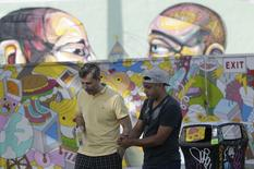Norvin Navarete (R) and his friend Stanmeir Dimov are seen in the Wynwood Walls art installation in Miami's Wynwood neighborhood, October 6, 2014. REUTERS/Andrew Innerarity