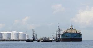 Нефтяной танкер в порту Pulau Sebarok в Сингапуре 18 апреля 2012 года. Аналитики резко снизили прогнозы цен на нефть после решения ОПЕК не сокращать добычу, показал опрос Рейтер. REUTERS/Tim Chong