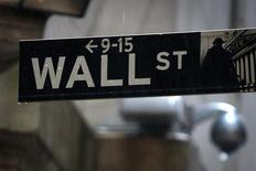 Una señalética de Wall Street fotografiada bajo la lluvia afuera de la bolsa de Nueva York. Imagen de archivo, 9 junio, 2014. Las acciones bancarias lideraban las alzas del viernes en Wall Street, después de que el dato de nóminas no agrícolas fue mucho mayor a lo anticipado, lo que aumentaba las expectativas del mercado de que un alza de las tasas de interés por parte de la Reserva Federal podría producirse antes de lo esperado.  REUTERS/Carlo Allegri