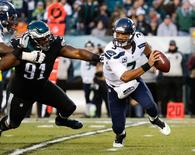 Seattle Seahawks quarterback Russell Wilson (3) eludes the pass rush of Philadelphia Eagles defensive end Fletcher Cox (91) during the first quarter at Lincoln Financial Field. Mandatory Credit: Bill Streicher-USA TODAY Sports