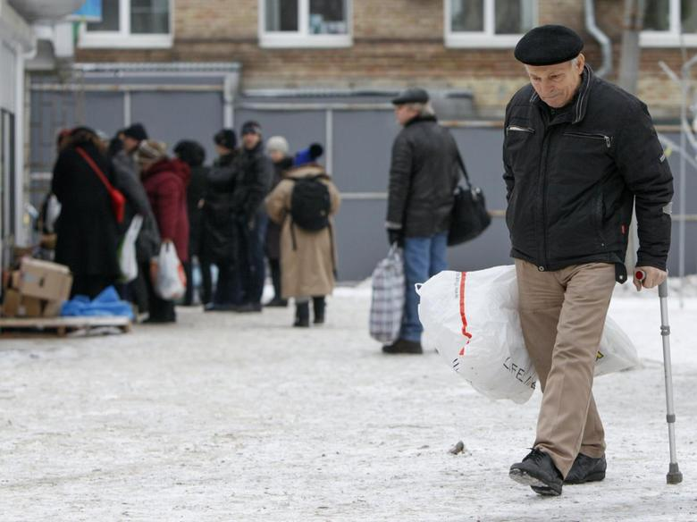 An internally displaced person (IDP) from eastern Ukraine walks with bags outside a volunteer centre in Kiev December 6, 2014. REUTERS/Valentyn Ogirenko