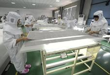 Employees process solar panel components at a solar power plant in Hefei, Anhui province July 26, 2012. REUTERS/Stringer