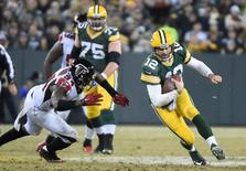 Dec 8, 2014; Green Bay, WI, USA;  Green Bay Packers quarterback Aaron Rodgers (12) scrambles for a first down against Atlanta Falcons linebacker Jonathan Massaquoi (94) in the second quarter at Lambeau Field. Mandatory Credit: Benny Sieu-USA TODAY Sports