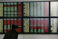 An investor looks at information displayed on an electronic screen at a brokerage house in Shanghai, December 8, 2014. REUTERS/Aly Song