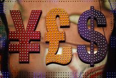 Символы валют доллар США, иена и фунт стерлингов у пункта обмена валюты в Гонконге 30 октября 2014 года. Правительство и Банк России уговаривают экспортеров более ритмично и равномерно продавать валюту, сказал премьер Дмитрий Медведев и пообещал скорую переоценку недооцененного рубля. REUTERS/Damir Sagolj