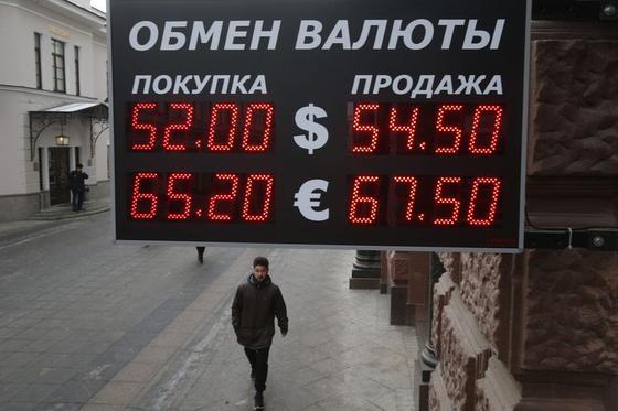 2014年12月3日,一名男子经过莫斯科一栋建筑上悬挂的卢布兑美元和欧元的汇率显示屏。REUTERS/Maxim Zmeyev