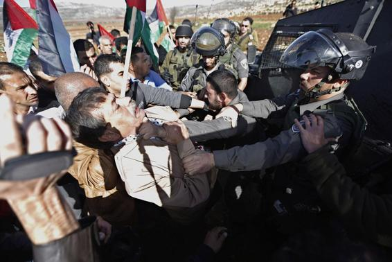 Palestinian minister Ziad Abu Ein (L) scuffles with an Israeli border policeman near the West Bank city of Ramallah December 10, 2014. REUTERS/Mohamad Torokman