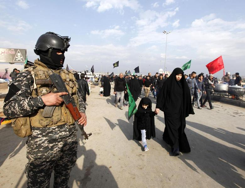 A police officer stands guard as Shi'ite pilgrims make their way to the holy city of Kerbala, ahead of the holy Shi'ite ritual of Arbaeen, in Baghdad, December 10, 2014. Arbaeen falls 40 days after the holy day of Ashura.   REUTERS/Ahmed Saad