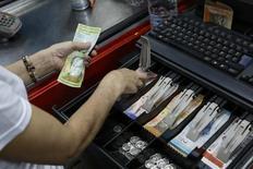 Una cajera contando bolívares en un supermercado en Caracas, sep 9 2014. Los precios de los bonos soberanos de Venezuela se han desplomado y el costo de asegurar la deuda contra una cesación de pagos se ha disparado, luego de que una caída de los precios del crudo a mínimos de cinco años recortó el flujo de efectivo al país empeorando la situación para una ya débil economía venezolana.  REUTERS/Carlos Garcia Rawlins