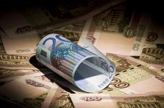 Купюры валют евро и рубль в Москве 17 февраля 2014 года. Рубль обновил абсолютные минимумы после повышения ключевой ставки ЦБР на 100 базисных пунктов до 10,5 процента годовых, поскольку ряд участников рынка ожидали более значительного ужесточения денежно-кредитной политики. REUTERS/Maxim Shemetov