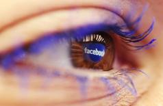 A Facebook logo reflected in the eye of a woman is seen in this picture illustration taken in Skopje November 6, 2014. REUTERS/Ognen Teofilovski