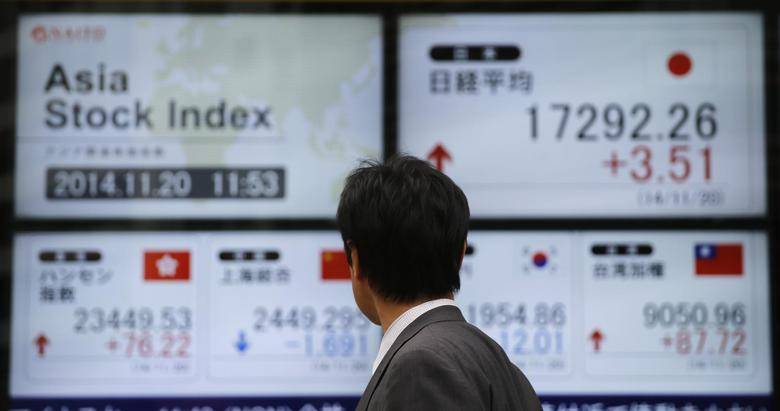 A man looks at electronic boards showing Asian stock indexes, outside a brokerage in Tokyo November 20, 2014.  REUTERS/Toru Hanai