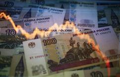 Рублевые купюры на фоне графика колебаний курса рубля к доллару в Варшаве 7 ноября 2014 года. Рубль дешевеет утром пятницы, обновив абсолютные минимумы на фоне приближения нефтяных котировок к самым низким значениям за последние 5,5 лет. REUTERS/Kacper Pempel