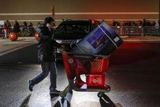 La confiance du consommateur américain s'est améliorée en décembre pour atteindre son plus haut niveau en près de huit ans grâce à une amélioration des perspectives pour l'emploi et les salaires et à la baisse des prix de l'essence. /Photo prise le 27 novembre 2014/REUTERS/Eduardo Munoz
