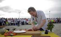 "The Naked Chef Jamie Oliver slices fish during an appearance on NBC's ""Today"" show in Miami Beach, Florida February 22, 2008. REUTERS/Eric Thayer"
