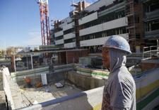 """Un trabajador mira en lo alto de una construcción de un edificio de viviendas en el barrio de Valdebebas, en Madrid el 10 de diciembre.  REUTERS/Andrea Comas. En una ajetreada calle en el centro de Madrid, Juan José Perucho muestra dónde va a construir uno de los bloques residenciales más altos de la capital tras adquirir en noviembre al público Metro de Madrid un terreno superior al espacio de cinco campos de fútbol. """"Hemos vendido más rápido que nunca en esta promoción"""", explica el jefe de la inmobiliaria IBOSA sobre la torre de 25 pisos con piscina y jardines verticales. """"No he visto nada igual en mis 24 años en este negocio"""". El país, tan acostumbrado a un paisaje coronado de grúas durante décadas, está volviendo tímidamente a la actividad después de siete años de una sequía histórica con el pinchazo de una burbuja inmobiliaria que desencadenó la mayor recesión desde la democracia. Entre los meses de junio y septiembre, la construcción residencial registró su primer aumento trimestral desde el comienzo de la crisis."""