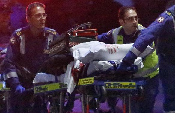 Paramedics remove a person, with bloodstains on the blankets covering the person, on a stretcher from the Lindt cafe, where hostages were being held, at Martin Place in central Sydney December 16, 2014.   REUTERS-David Gray