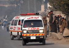 """Машины """"скорой помощи"""" отъезжают от атакованной талибами школы в Пешаваре 16 декабря 2014 года. По меньшей мере 84 ребенка погибли в результате захвата заложников боевиками исламистского движения """"Талибан"""" в военной школе в пакистанском Пешаваре во вторник, сообщили местные власти. REUTERS/Khuram Parvez"""