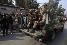 """Сотрудники служб безопасности Пакистана у атакованной талибами школы в Пешаваре 16 декабря 2014 года. По меньшей мере 126 человек, из них более 100 детей, погибли в результате захвата заложников боевиками исламистского движения """"Талибан"""" в военной школе в пакистанском Пешаваре во вторник, сообщили местные власти. REUTERS/Fayaz Aziz"""