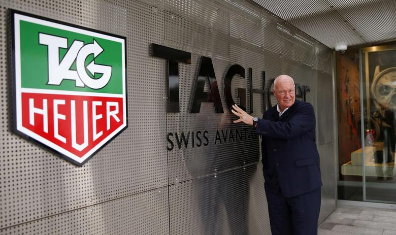 Jean-Claude Biver, head of French luxury goods group LVMH's watch business and interim CEO of the group's biggest watch brand, TAG Heuer, poses in front of the company's logo before a news conference in the western Swiss town La Chaux-de-Fonds December 16, 2014.    REUTERS/Arnd Wiegmann
