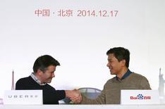Le directeur général d'Uber Travis Kalanick (à gauche) et celui de Baidu, Robin Li. Le géant chinois de l'internet a pris une participation dans le service de voiturage, alors que les deux sociétés veulent profiter de la croissance dans l'un des premiers marchés mondiaux des transports. /Photo prise le 17  décembre 2014/REUTERS/Kim Kyung-Hoon