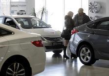 Люди в дилерском центре Hyundai в Ставрополе 17 декабря 2014 года. Несколько иностранных автопроизводителей, включая американский General Motors, остановили оптовые продажи автомобилей дилерам из-за обвала рубля, другие вынуждены пересматривать цены почти каждый день. REUTERS/Eduard Korniyenko