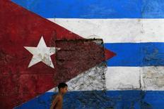 Мальчик проходит мимо выкрашенной в цвета кубинского флага стены в Гаване 21 октября 2012 года. США и Куба приняли решение помириться спустя более чем 50 лет с момента резкого ухудшения отношений, должен сказать президент Барак Обама в обращении в среду. REUTERS/Enrique De La Osa