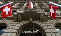 National flags of Switzerland fly over the entrance of the headquarters of Swiss bank Credit Suisse in Zurich July 31, 2014.  REUTERS/Arnd Wiegmann