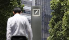 Un hombre camina frente a un logo del Deutsche Bank en Tokio. Imagen de archivo, 16 julio, 2014. Deutsche Bank anunció el jueves que revisará su estrategia y sus objetivos de ganancias el próximo año y que podría vender su unidad minorista Postbank.  REUTERS/Toru Hanai