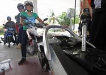 An employee of state-owned Pertamina refuels a motorcycle at its petrol station in Jakarta, December 17, 2014. REUTERS/Pius Erlangga