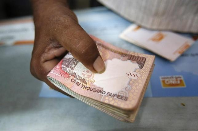 A customer hands a bundle of rupee currency notes to a teller at a financial institution in Mumbai July 2, 2013. REUTERS/Vivek Prakash/Files