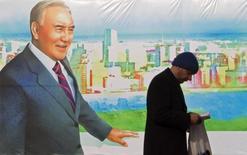 Мужчина читает книгу на фоне постера с изображением президента Казахстана Нурсултана Назарбаева в Алма-Ате 28 ноября 2012 года. Богатый нефтью Казахстан подготовил экономический план, предполагающий снижение мировой цены на нефть до $40 за баррель, сказал бессменный президент страны Нурсултан Назарбаев, пообещав не урезать социальные программы. REUTERS/Shamil Zhumatov