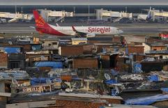 A SpiceJet passenger aircraft taxis on the runway at the airport next to a slum area in Mumbai December 19, 2014.  REUTERS/Shailesh Andrade