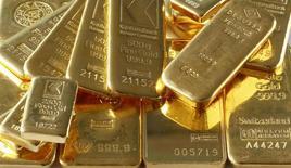Слитки золота в банковском хранилище в Цюрихе 20 ноября 2014 года. Цены на золото растут благодаря снижению курса доллара к евро, но подъем на фондовых рынках сдерживает рост котировок. REUTERS/Arnd Wiegmann