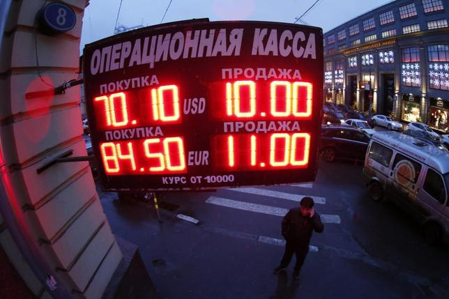 A man stands next to a building under a board showing currency exchange rates in Moscow, December 16, 2014.  REUTERS/Maxim Zmeyev