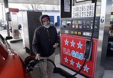 A gas station attendant fills a customer's vehicle in Turnersville, New Jersey December 4, 2014.  REUTERS/Tom Mihalek