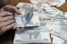 Сотрудник ставропольской компании считает рубли 17 декабря 2014 года. Правительство РФ потребовало от пяти госкомпаний к весне избавиться от скупленной за время обвальной девальвации валюты - довести чистые валютные активы до уровня начала октября и более не превышать его. REUTERS/Eduard Korniyenko